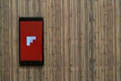 在智能手机屏幕上的Flipboard商标在木背景 免版税图库摄影