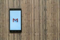 在智能手机屏幕上的Gmail商标在木背景 免版税库存图片