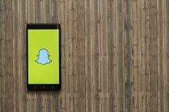 在智能手机屏幕上的Snapchat商标在木背景 库存照片