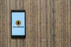 在智能手机屏幕上的Soundhound商标在木背景 免版税库存照片