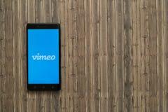 在智能手机屏幕上的Vimeo商标在木背景 免版税库存图片