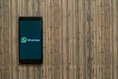 在智能手机屏幕上的Whatsapp商标在木背景 库存图片