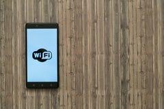 在智能手机屏幕上的Wifi商标在木背景 免版税库存照片