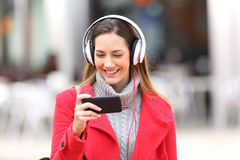 在智能手机或听的音乐的女孩观看的录影 免版税库存照片