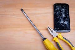 在智能手机旁边是螺丝刀和钳子和一把锤子,在木背景 免版税库存图片
