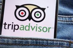 在智能手机显示的Tripadvisor商标掩藏在牛仔裤装在口袋里 免版税图库摄影