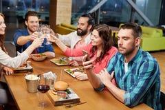 在智能手机的人传讯在餐馆 免版税库存图片