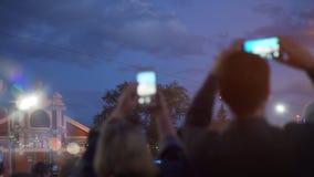 在智能手机的人射击的街道音乐会 股票录像