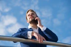 在智能手机的商人谈话 有手机的人在蓝天 在蓝色衣服的上司在晴朗室外 营业通讯,新 图库摄影