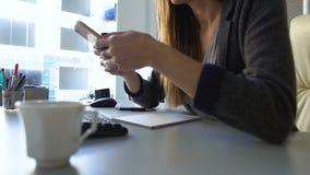 在智能手机的女性办公室工作者读书新闻,等待另一个客户 股票视频