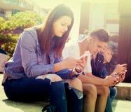 在智能手机的少年戏剧在校园 图库摄影