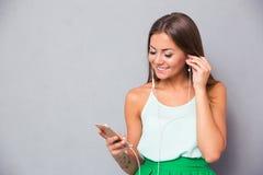 在智能手机的微笑的女孩听的音乐 库存照片