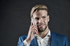 在智能手机的愉快的人谈话 与手机的商人微笑 企业生活方式概念 营业通讯和新的技术 免版税库存图片