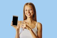 在智能手机的愉快的微笑的妇女点,被隔绝在蓝色背景 库存图片