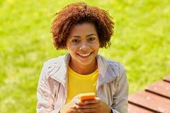 在智能手机的愉快的非洲少妇传讯 免版税库存照片