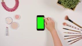 在智能手机的手指卷动有绿色屏幕的 免版税库存照片