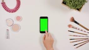在智能手机的手指卷动有绿色屏幕的 库存图片