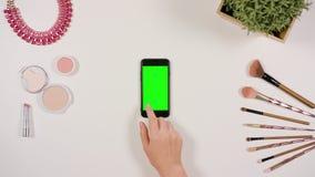 在智能手机的手指卷动有绿色屏幕的 图库摄影