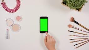 在智能手机的手指卷动有绿色屏幕的 库存照片