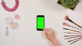 在智能手机的手指卷动有绿色屏幕的 免版税库存图片