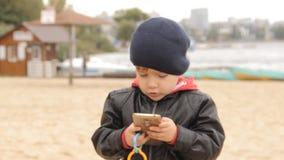 在智能手机的按钮吹他的面颊和集合的男孩是平直的盖帽 股票录像