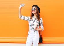 在智能手机的时髦少妇式样采取的图片自画象在五颜六色的桔子的佩带的黑帽会议白色裤子 免版税库存照片