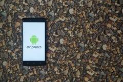 在智能手机的机器人商标在小石头背景  免版税库存照片