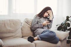 在智能手机的沮丧的妇女读书消息 库存图片
