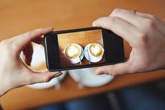 在智能手机的热奶咖啡 免版税库存照片