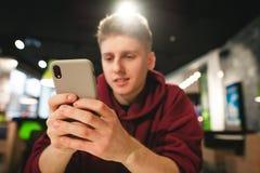 在智能手机的焦点,正面人使用智能手机的互联网 年轻人在便当咖啡馆使用一个智能手机 库存图片
