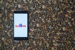 在智能手机的百度商标在小石头背景  库存图片