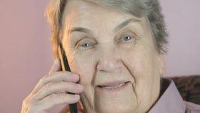 在智能手机的祖母微笑的谈话 关闭 股票视频
