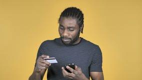 在智能手机的网络购物由在黄色背景隔绝的偶然非洲人 股票视频