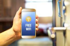 在智能手机的自由旅馆wifi在旅馆客房 免版税库存照片