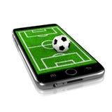 在智能手机的足球,体育App 图库摄影