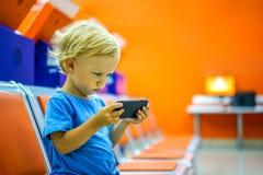 在智能手机的逗人喜爱的小男孩观看的动画片在休息室 库存图片