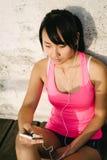 在智能手机的年轻女运动员messagin 库存照片