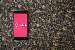 在智能手机的Airbnb商标在小石头背景  免版税库存图片