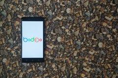 在智能手机的Badoo商标在小石头背景  免版税库存照片