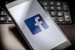 在智能手机的Facebook页在桌上 免版税库存图片