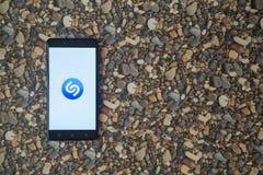 在智能手机的Shazam商标在小石头背景  库存图片