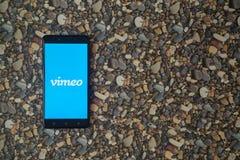 在智能手机的Vimeo商标在小石头背景  图库摄影
