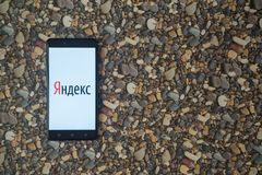 在智能手机的Yandex商标在小石头背景  免版税库存照片