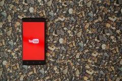 在智能手机的Youtube商标在小石头背景  免版税库存图片