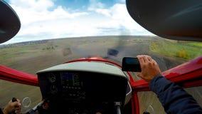 在智能手机pov,极端爱好,航空的男性摄制的体育平面着陆 免版税库存照片