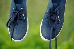 在晾衣绳的肮脏的蓝色运动鞋 图库摄影