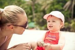 在暑假期间,婴孩与热带海滩的母亲沟通 免版税库存照片