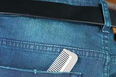 在暗色的蓝色牛仔布牛仔裤与在场面的梳子提出Th 免版税库存照片