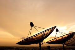在暮色天空的卫星盘剪影 免版税库存照片