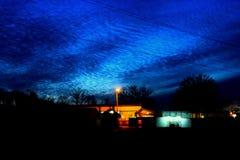 在暮色天空的波浪云彩 免版税库存照片